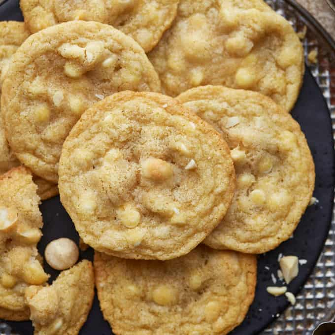 A half dozen cookies arranged on a black and silver serving plate