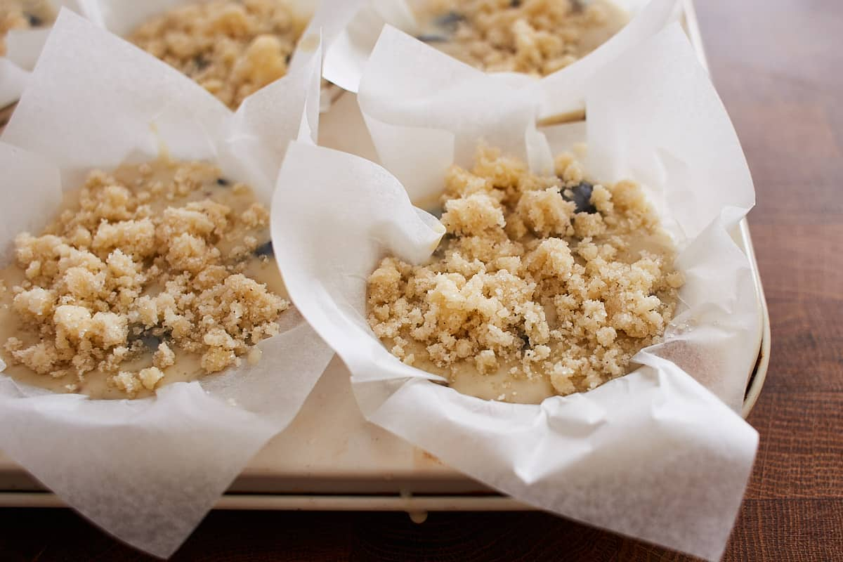 Unbaked muffin batter topped with streusel in a muffin pan