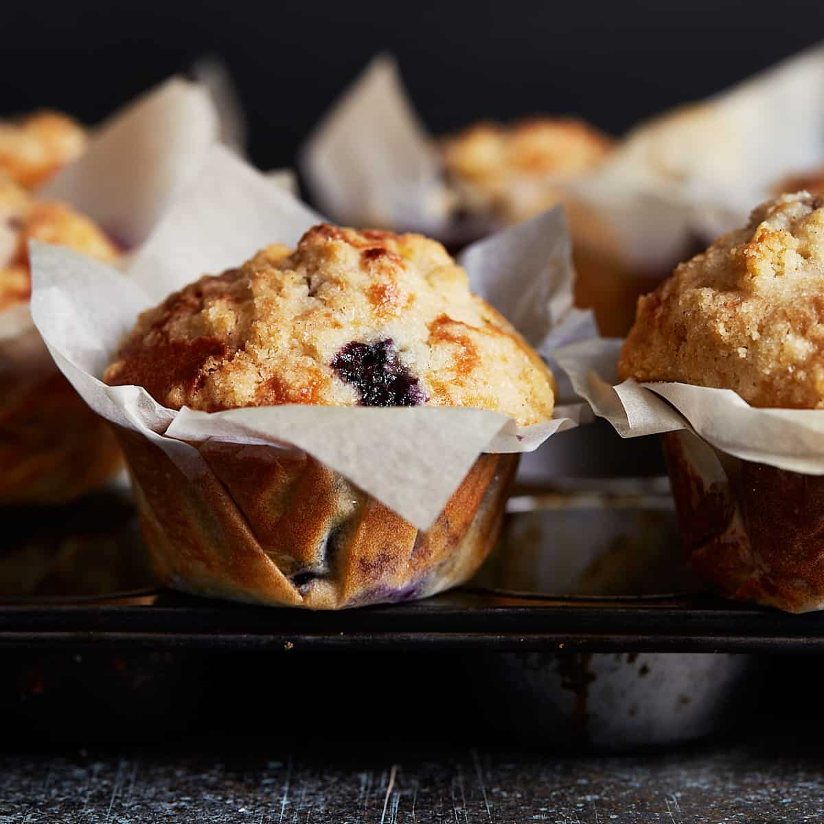 Muffin wrapped in paper on dark background