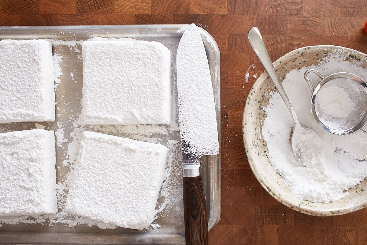 Cut pieces of marshmallow and a long sharp knife on a tray
