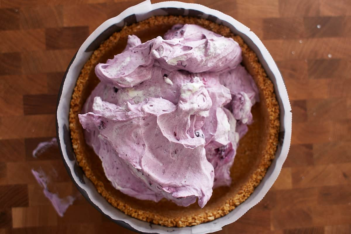 Blueberry filling scooped into a graham cracker crust