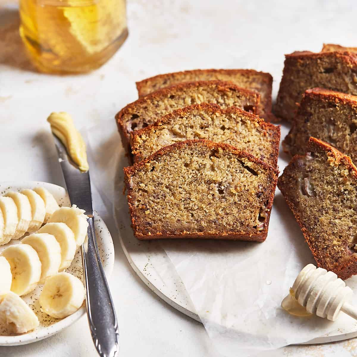 Slices of banana bread on a serving plate with butter, honey, and bananas
