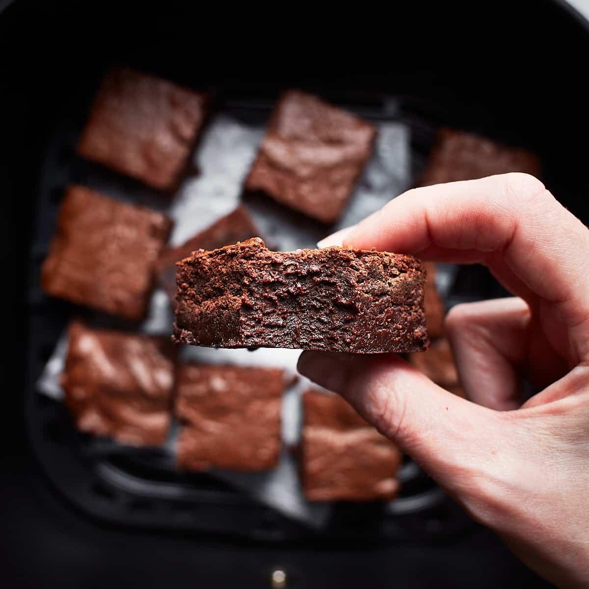 Holding a bitten brownie between fingers