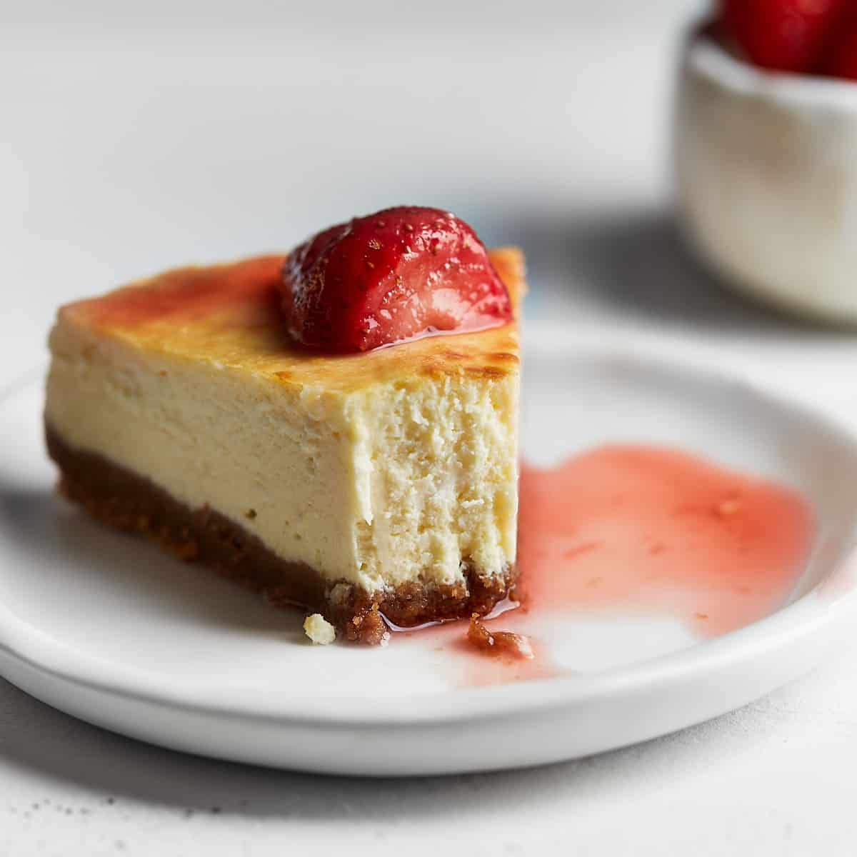 A slice of cheesecake on a plate with a piece bitten out