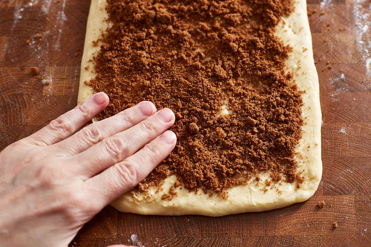 Pressing cinnamon sugar onto a rolled out and buttered dough