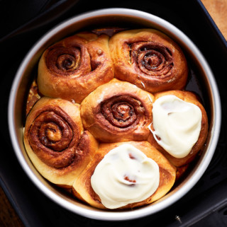 Baked rolls, two of them glazed, in an air fryer basket