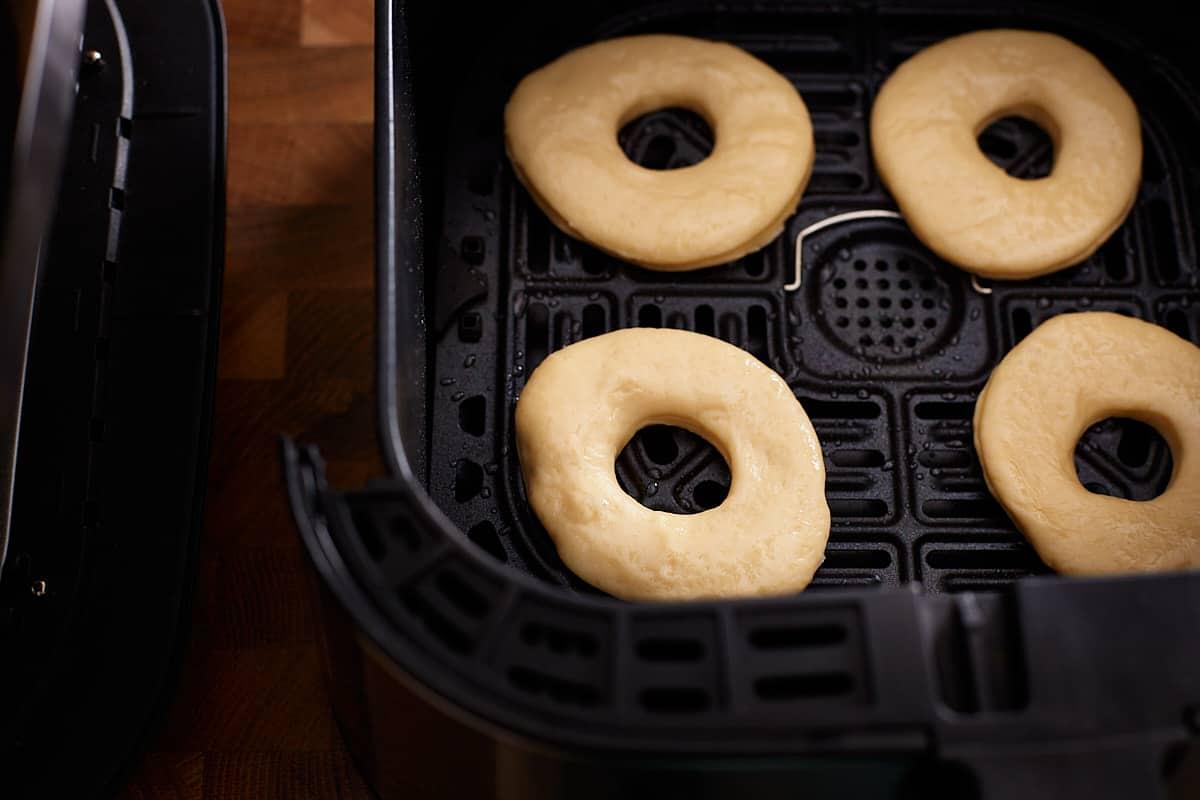 Raw donut dough in an air fryer basket