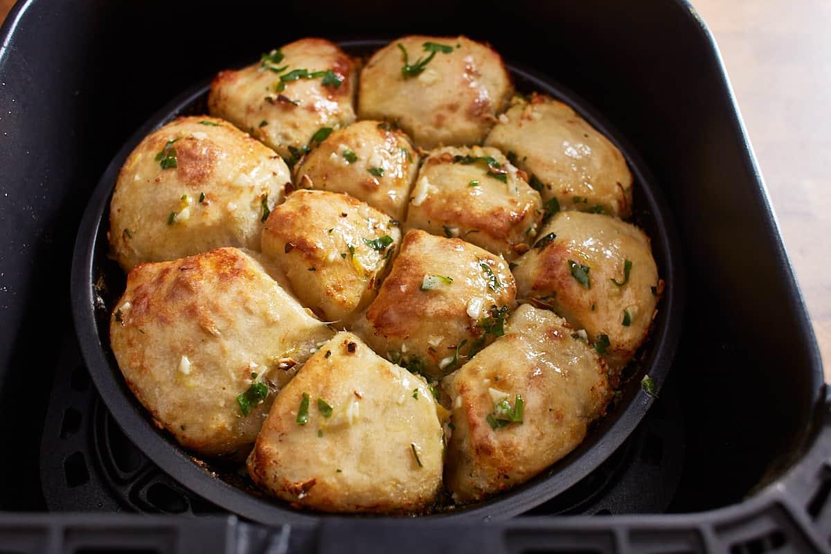 Half baked garlic bread in an air fryer basket