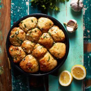 Balls of garlic bread in a baking pan with parsley, garlic, and lemon decoration