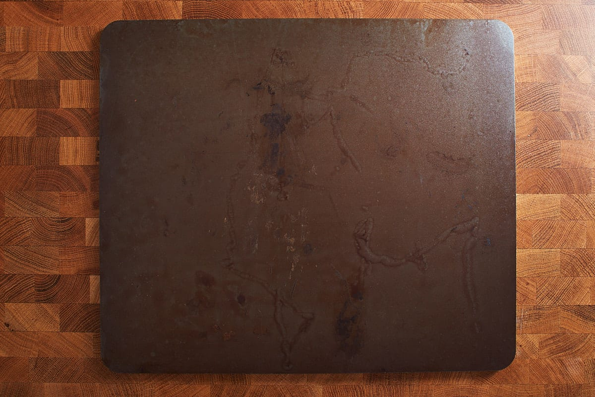 pizza steel on a wooden surface