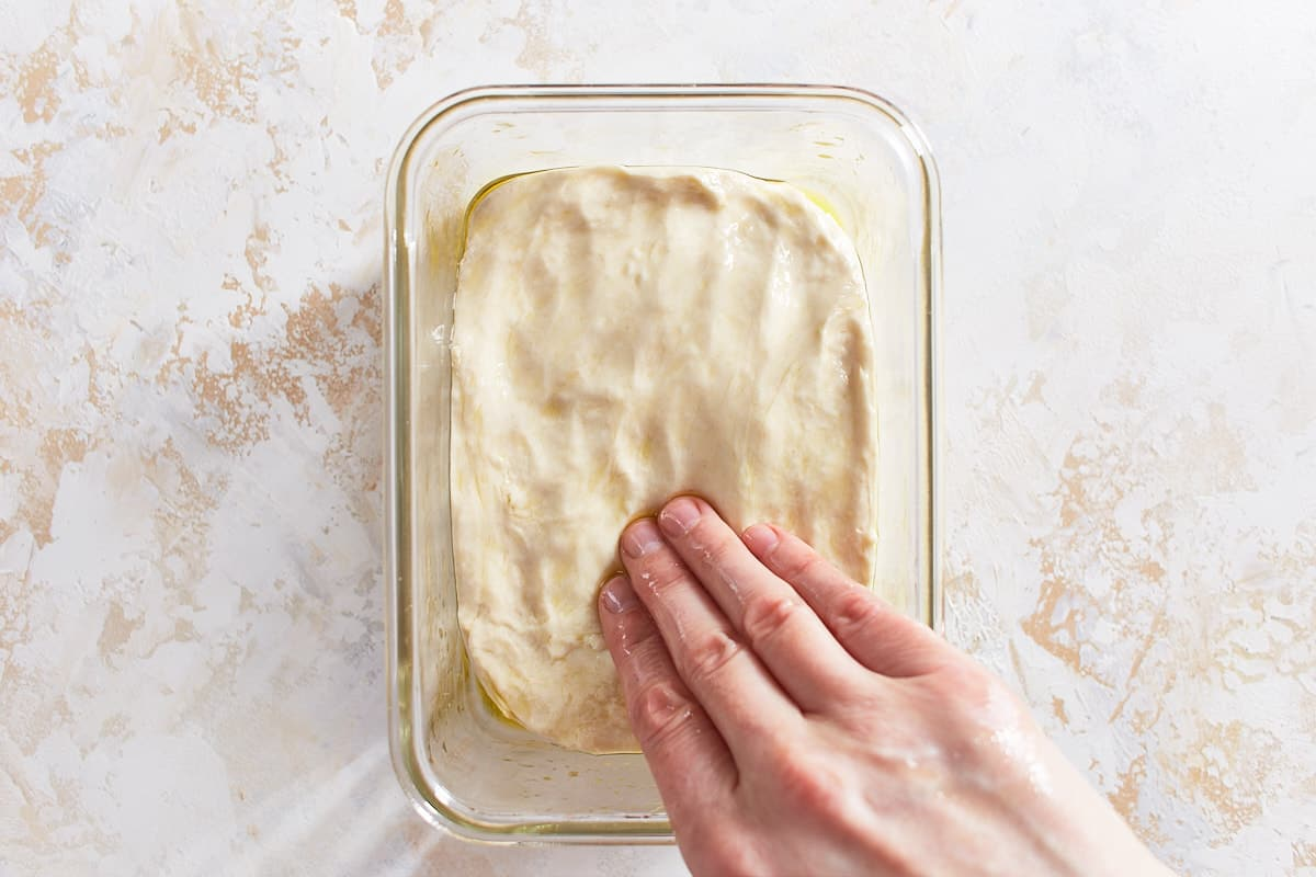 Pressing dough into the bottom of a straight sided vessel