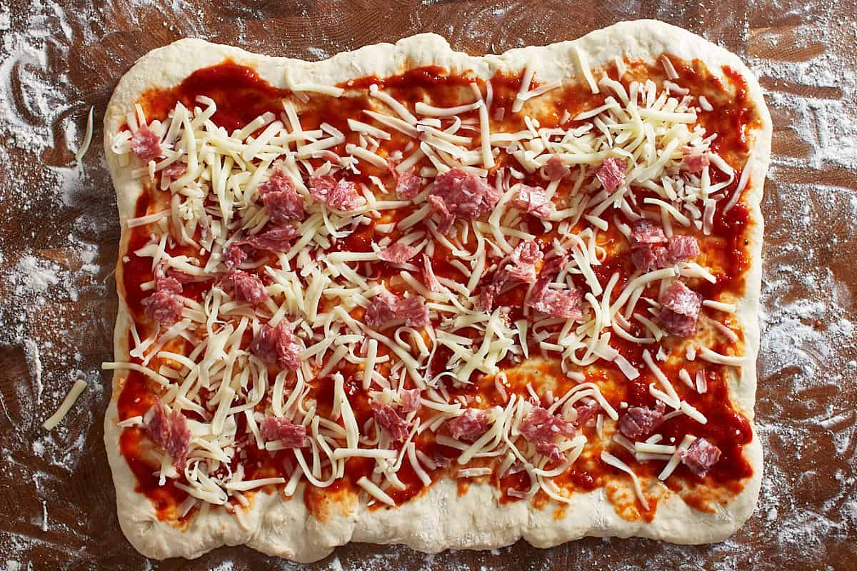 Raw dough topped with tomato sauce, cheese, and pepperoni