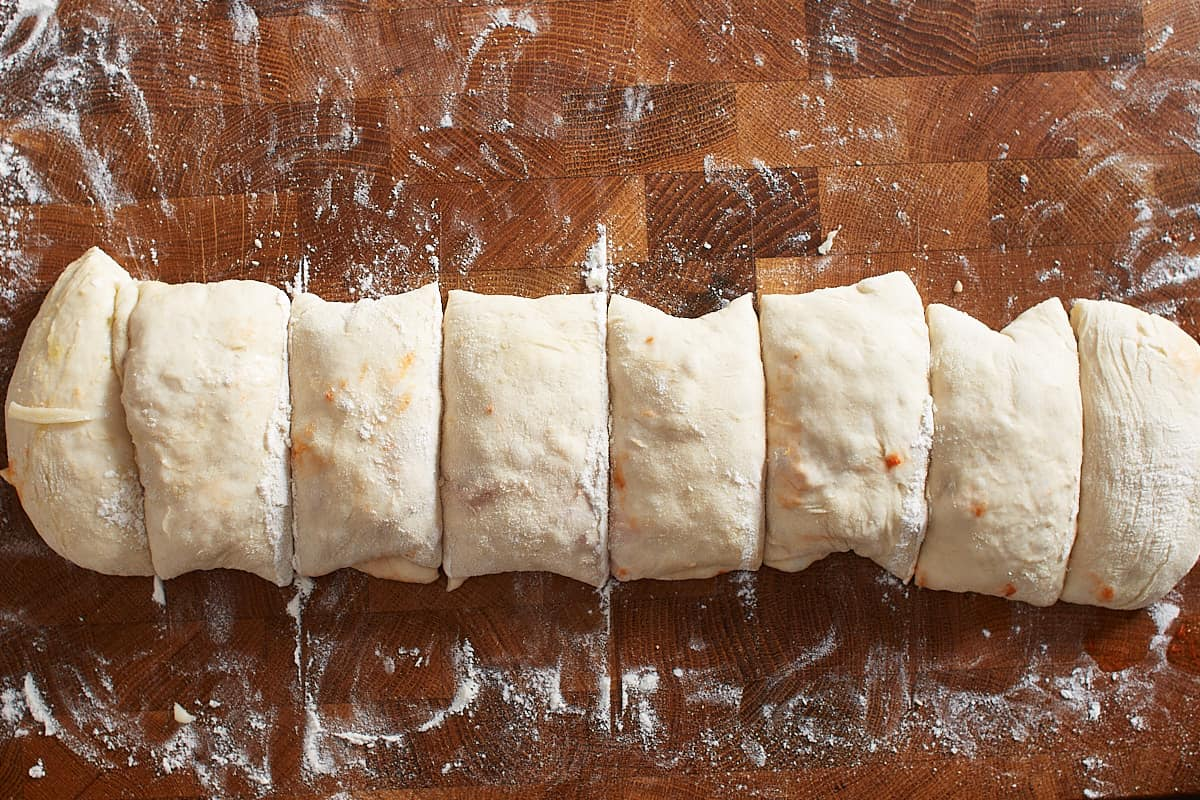 Rolled up pizza dough log cut into equal pieces