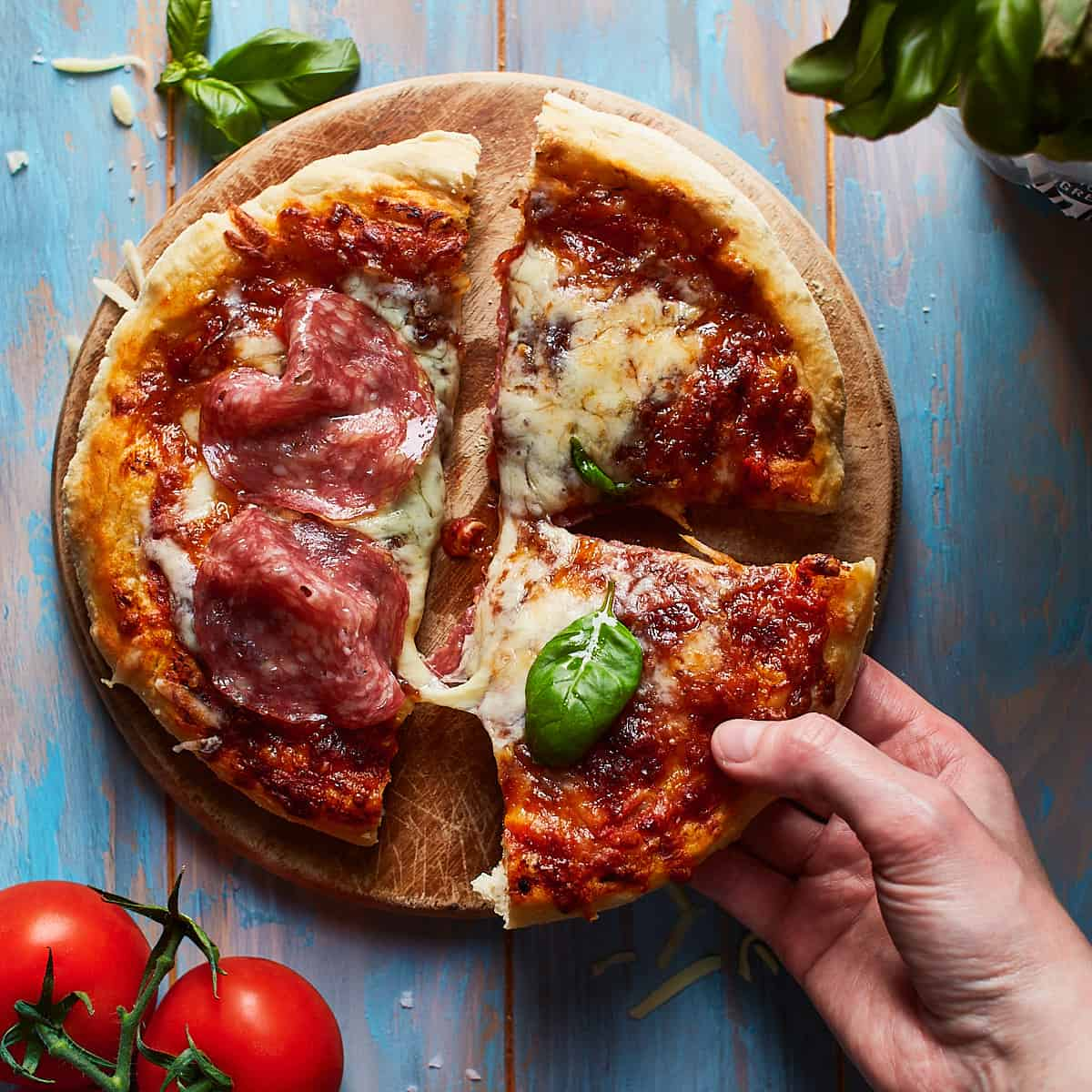 Lifting up a slice of pizza from a cutting board