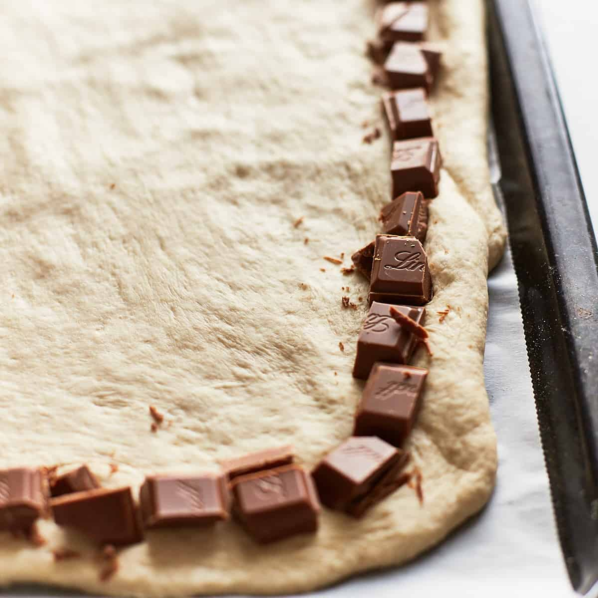 Chocolate pieces placed along the edge of a raw pizza dough