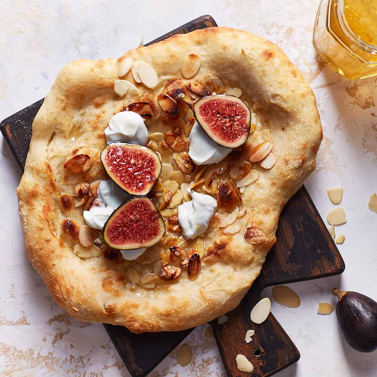Baked honey pizza with figs and goat cheese topping on a serving board