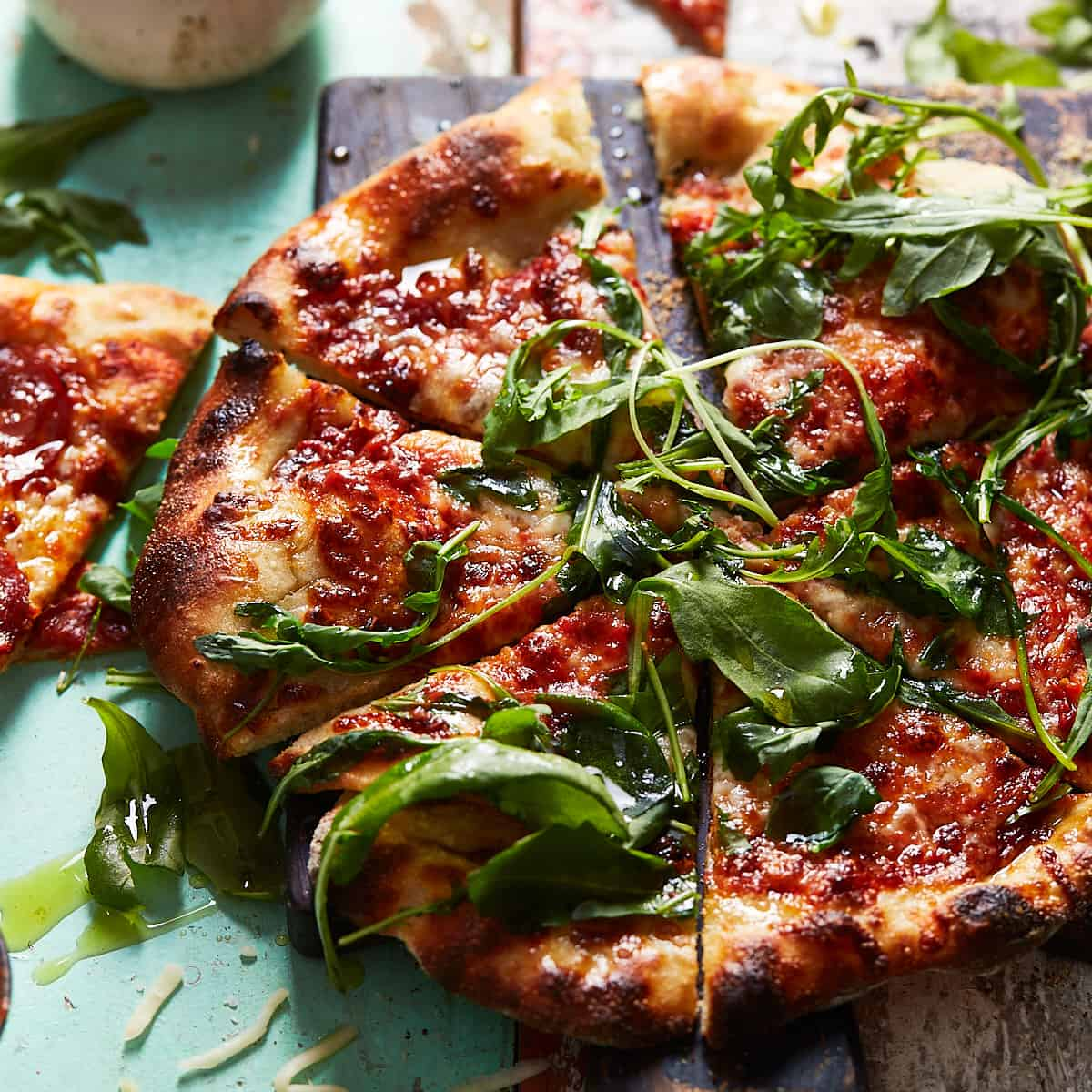 Sliced pizza with fresh rocket on top