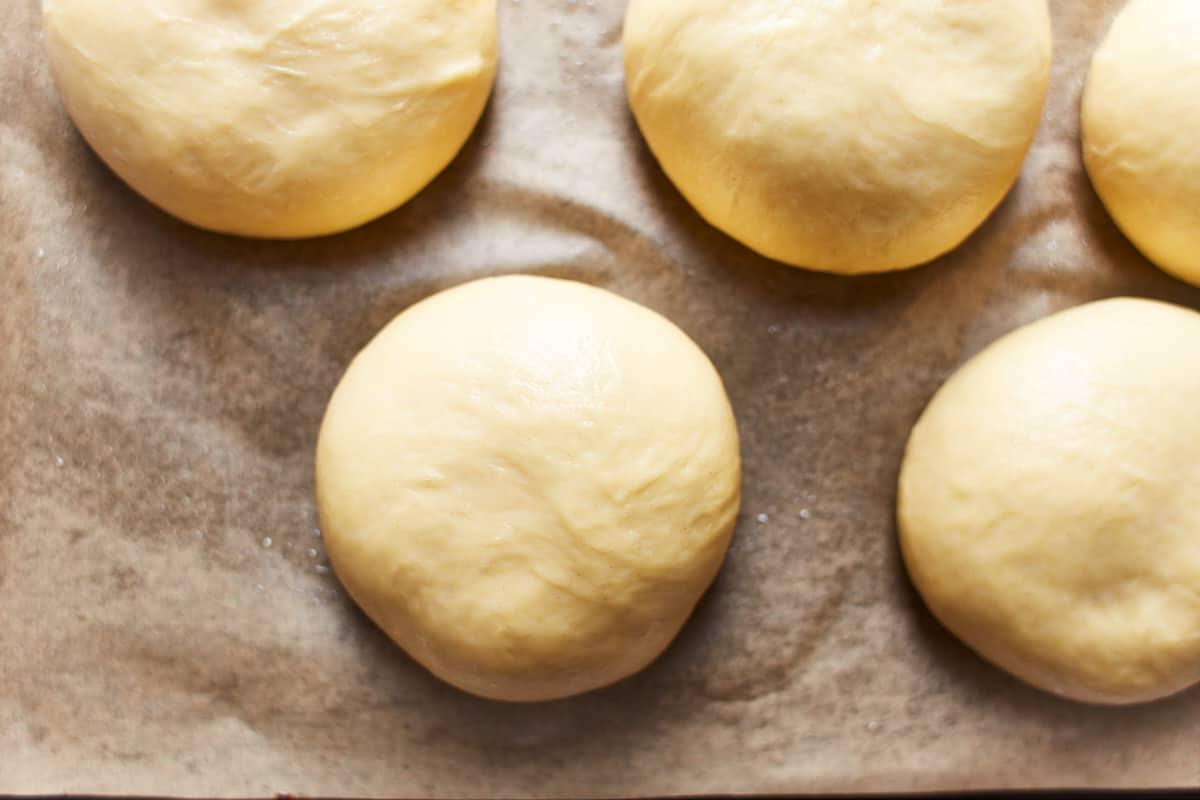 Risen balls of dough on a baking sheet