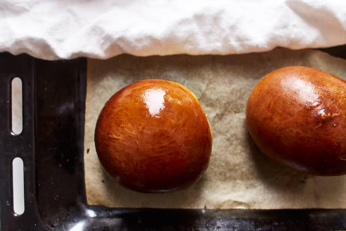 Baked brioche rolls on a baking sheet