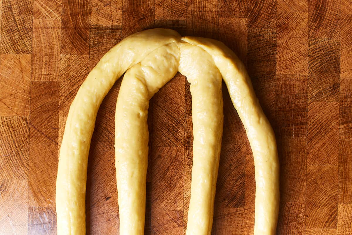 Four dough strands pinched together on one side