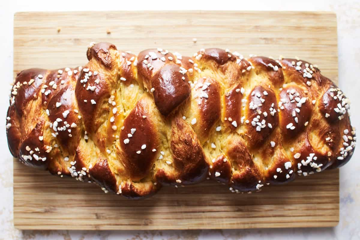 Baked loaf of challah on a cutting board