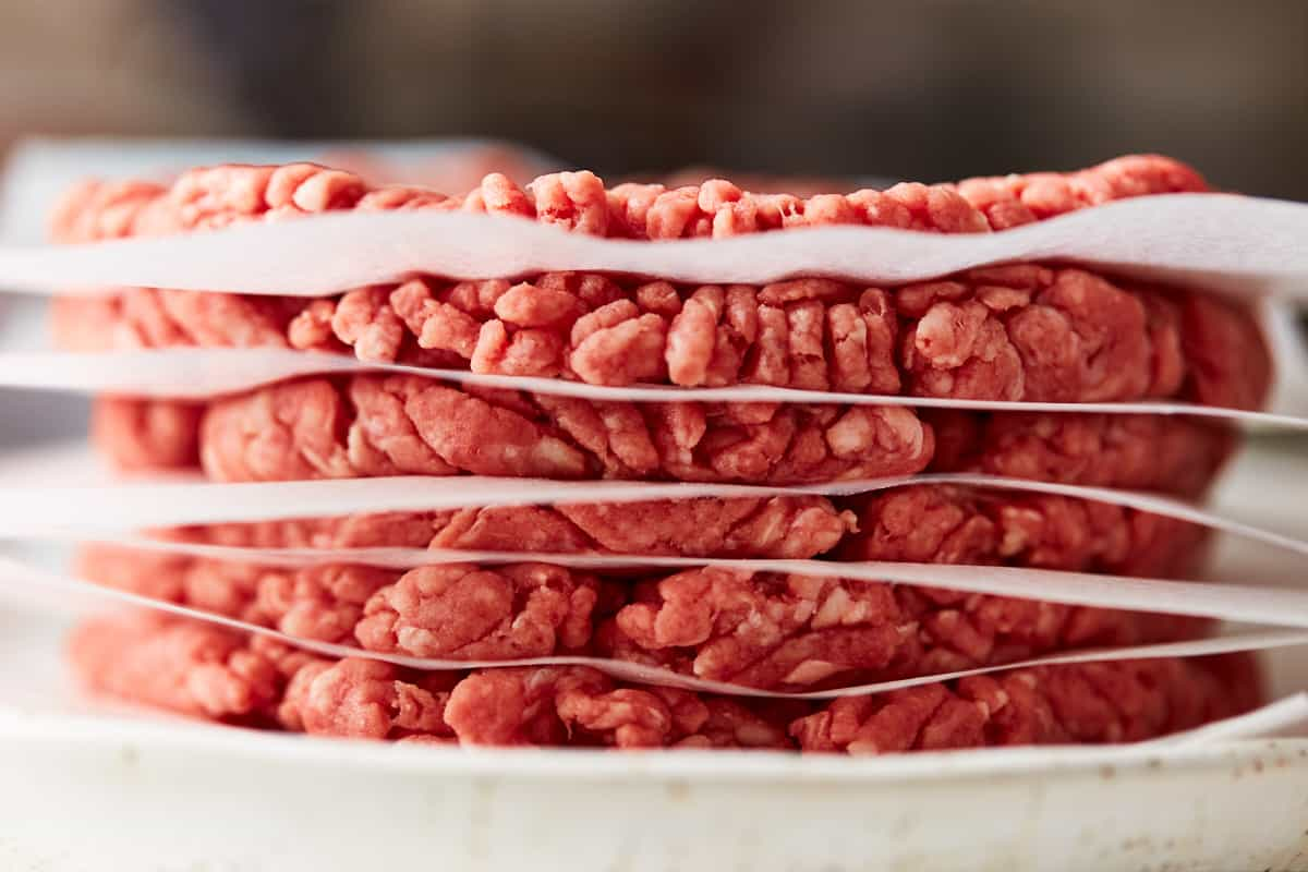 Stack of meat patties with wax paper in-between