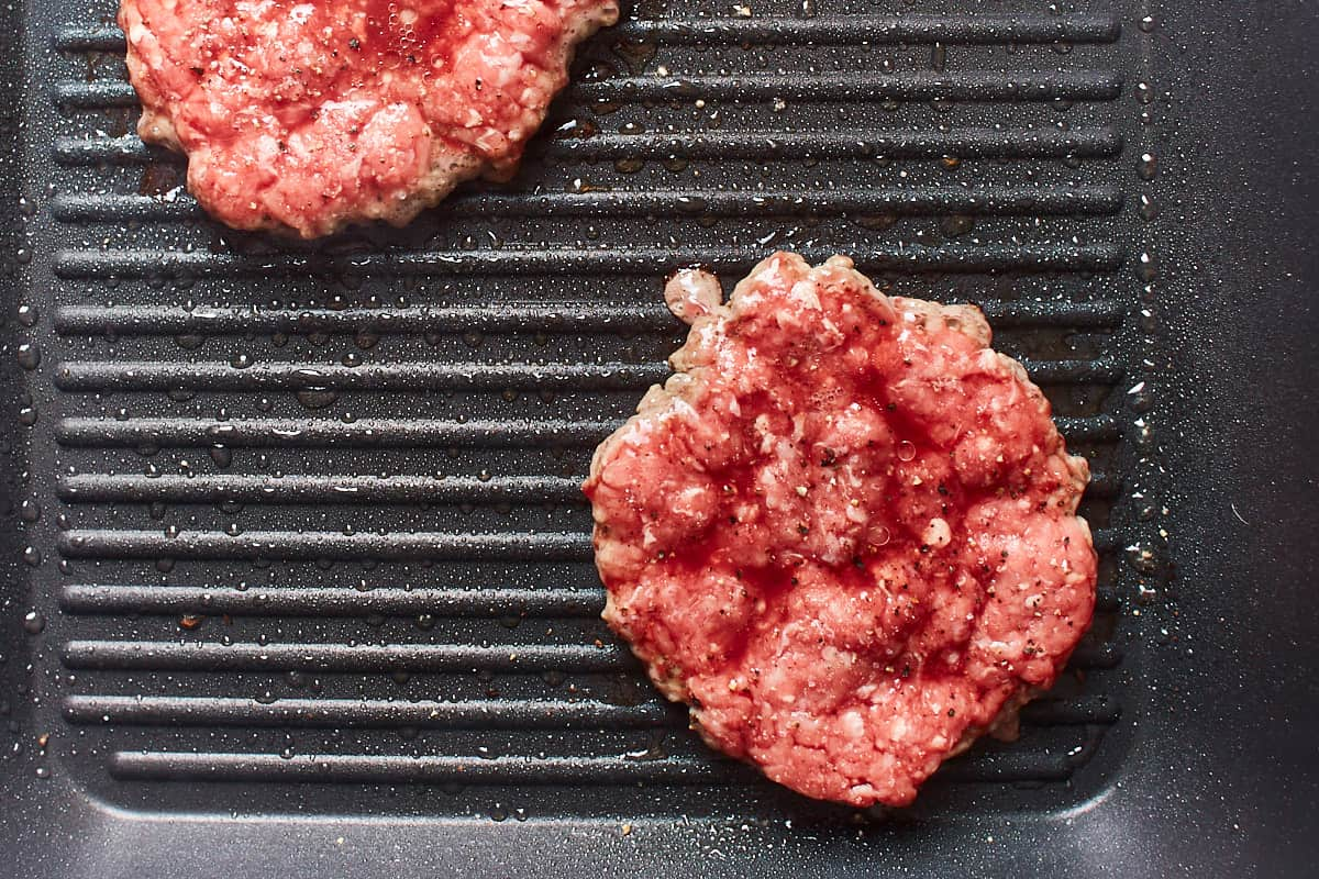 Half cooked hamburgers in a grill pan