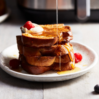 Pouring maple syrup over a stack of freshly cooked French toast