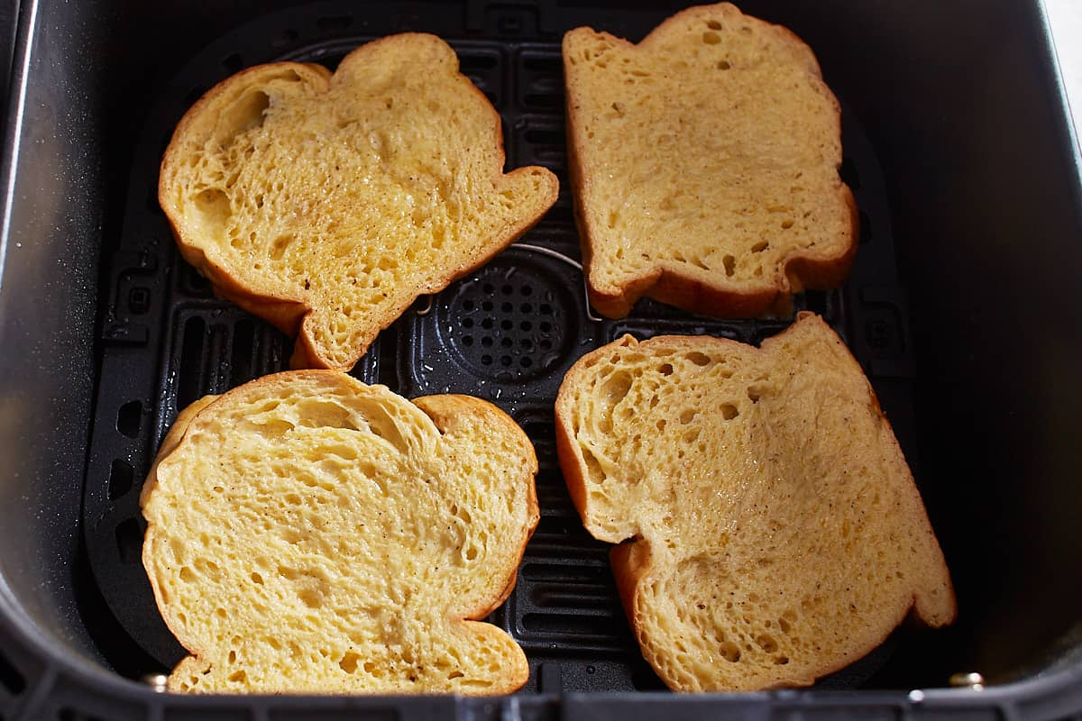 Four slices of French toast arranged in an air fryer basket