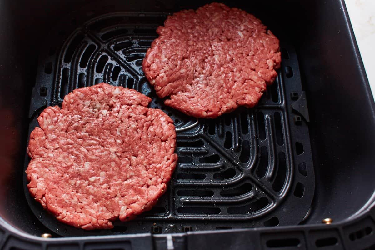 Fresh beef patties in an air fryer basket