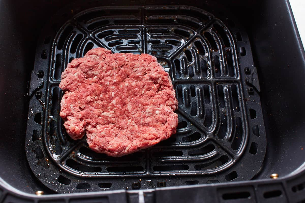 Frozen beef patty in an air fryer basket