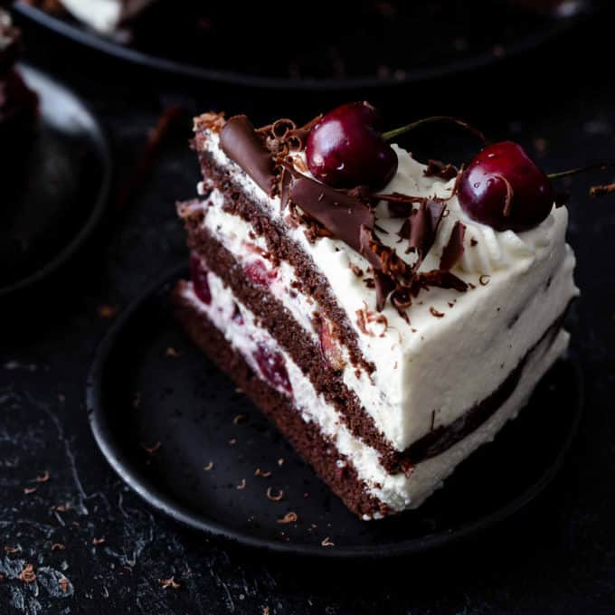 A slice of Black Forest cake on a black plate