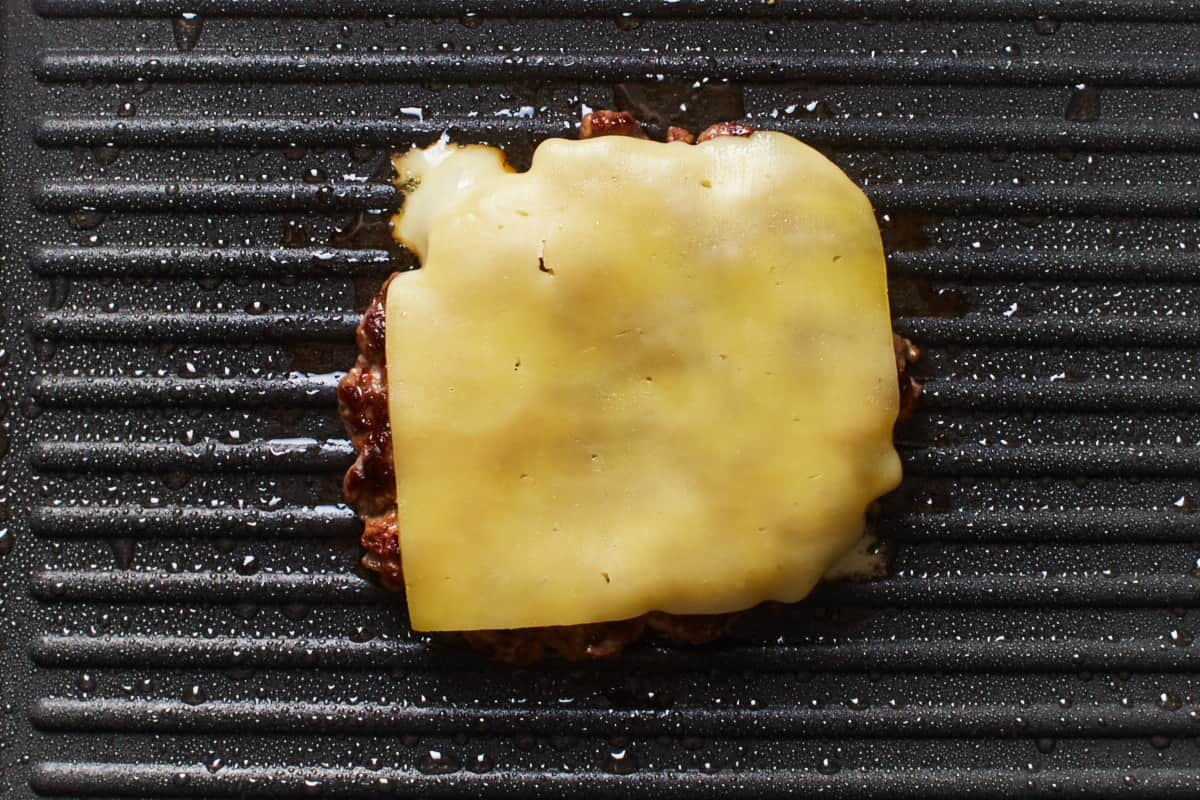 Beef patty with a slice of cheese on top in a pan