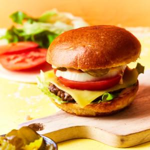A prepared cheeseburger on a serving board