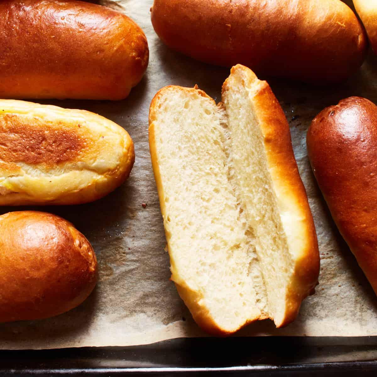 Split bread roll on a baking sheet