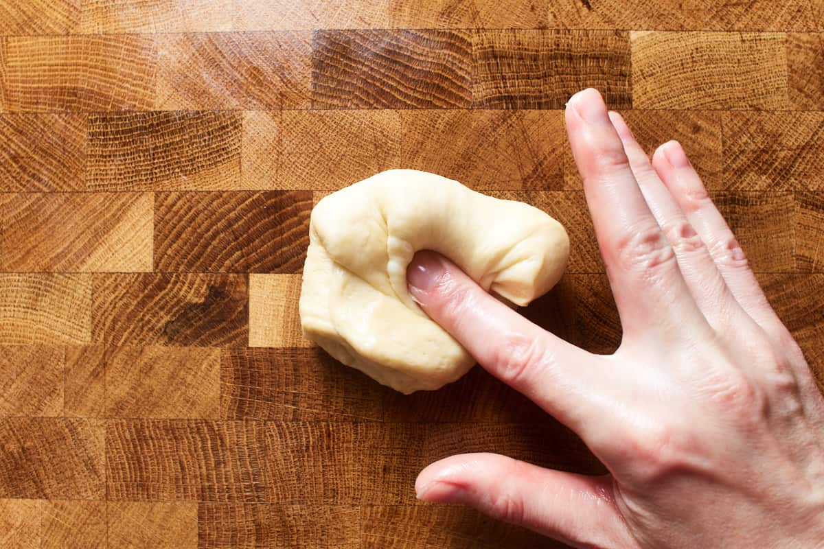 Folding a piece of dough over itself and over the center