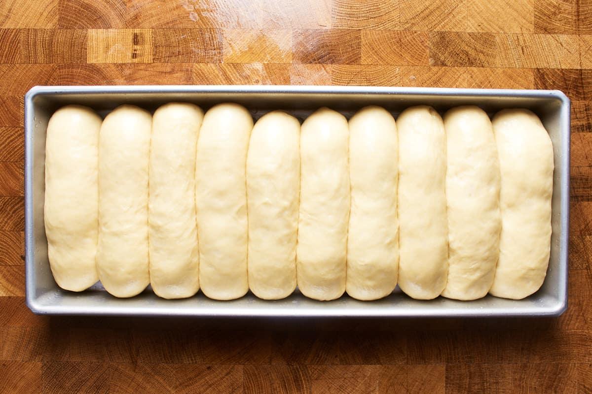 Risen hot dog rolls in a pan