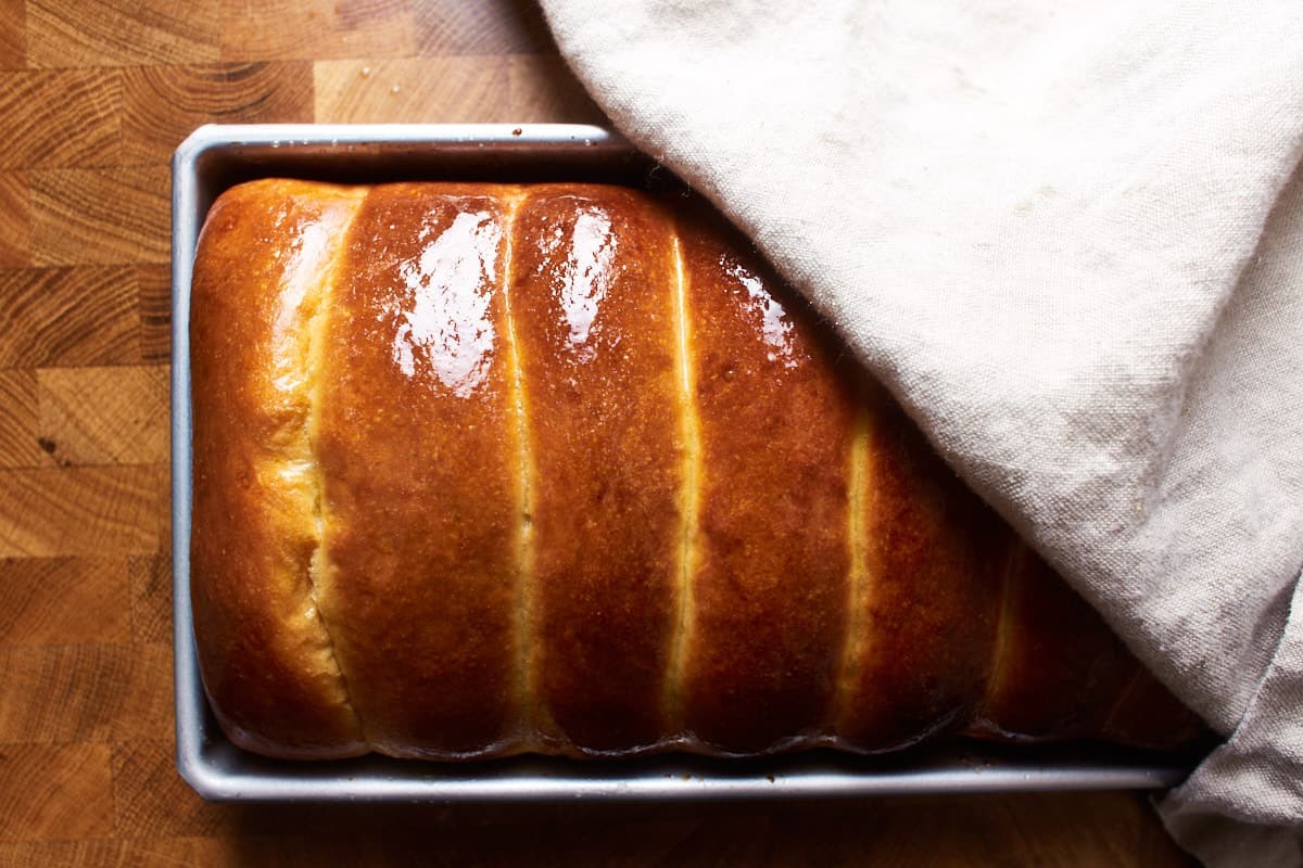 Buttered split top buns in a baking pan