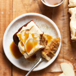 A slice of frosted apple cake with caramel syrup on a plate with a bite missing