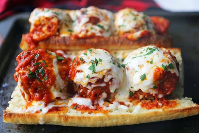 Meatballs covered in sauce and cheese on a hoagie roll