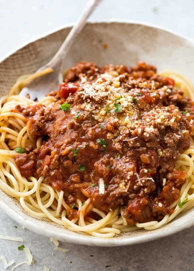 A plate full with spaghetti covered in bolognese sauce