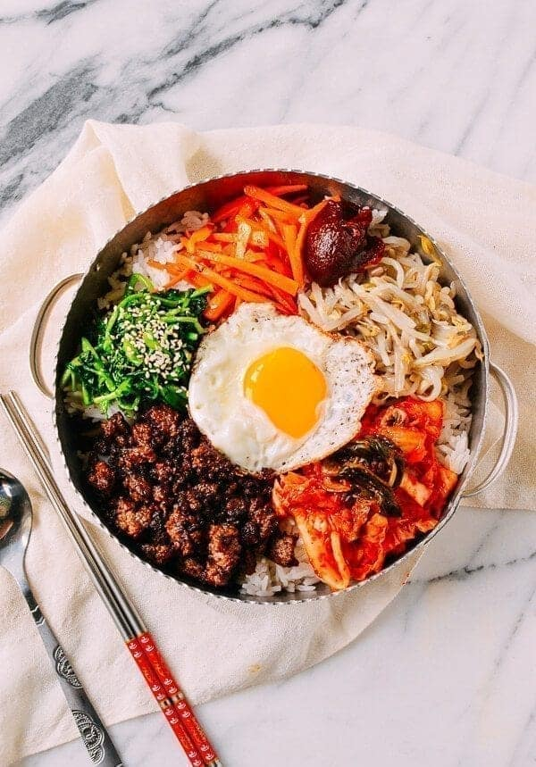 A bowl of bibimbap on a marbled table